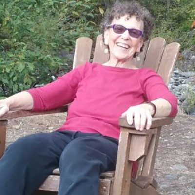 Image of Sooz Appeal reclining in a adirondack chair outside