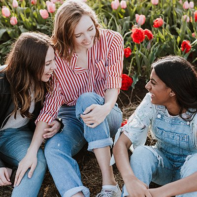 Three teenage girls sit in a tulip field laughing