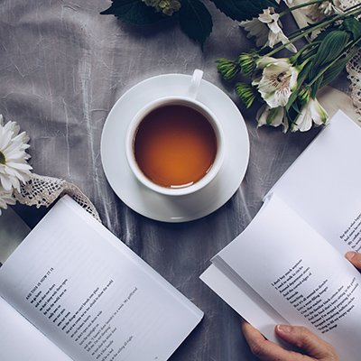 a cup of tea, two open face books, a bouquet of white daisy flowers, and a couple of doilies