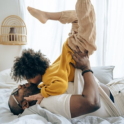 A black father plays with his son in bed