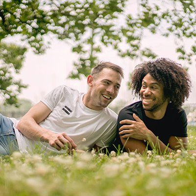 A gay inter-racial male couple smile and look at each other while laying on a field of grass