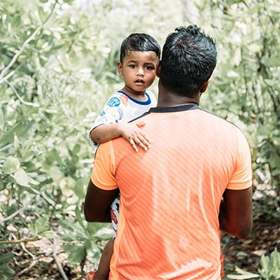 An Indian man holds his young son in dense brush