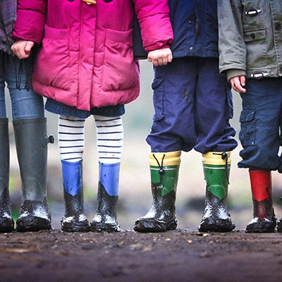 image of four children standing in mud all in their rain boots