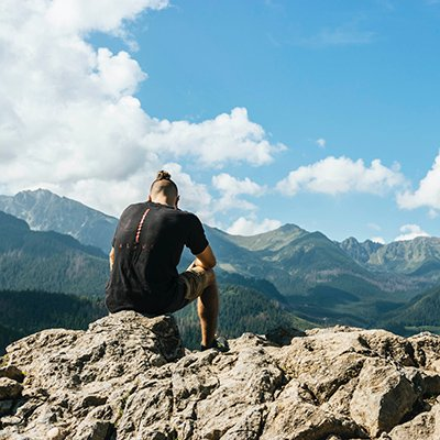 A young man sits on a boulder looking out at the mountain rage in the distance