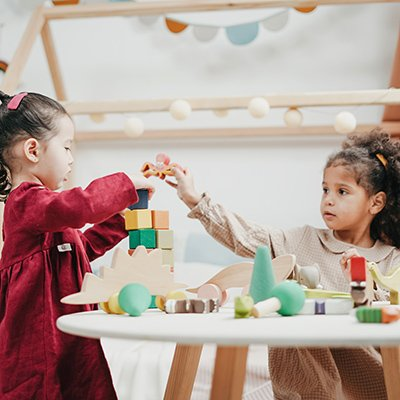 Two little girls playing with wooden blocks