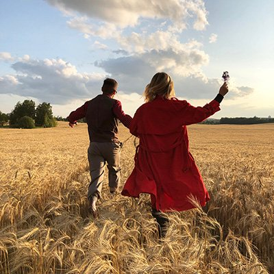 A young couple frolic through a field of wheat