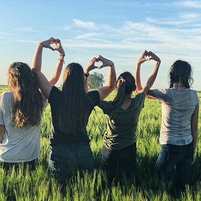 Four teenage girls stand in a field of grass hold their arms up and shape their hands into hearts