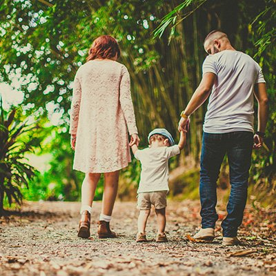 A young white couple walking with their toddler between them down a dirt path with foliage on either side of them
