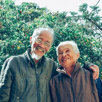 An elderly Asian couple hugs and smiles at the camera