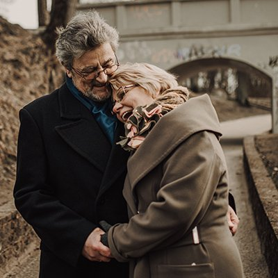 An elderly white couple embrace and smile
