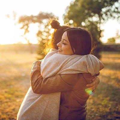 Two young caucasian beautiful women hugging in public park. Autumn time.