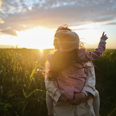 A woman gives a young girl a piggyback ride in a field of grass at sunset