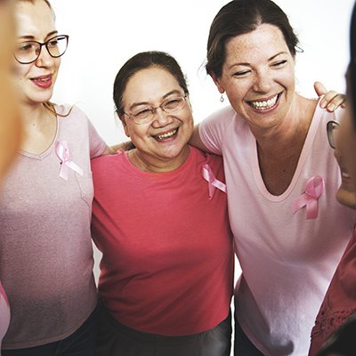 a group of women all wearing pink with the breast cancer ribbon pinned on their shirts are hugging and smiling
