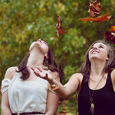 Women throwing fallen autumn leaves into the air
