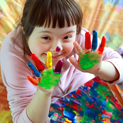 A child with down-syndrome finger painting