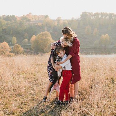 A lesbian couple hug with their son and dog