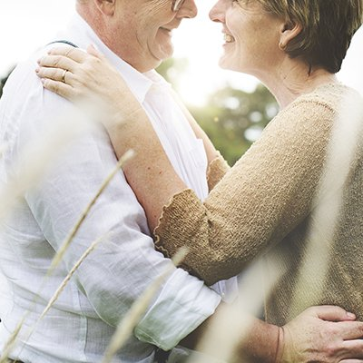 A elderly couple embrace and stare into each other's eyes